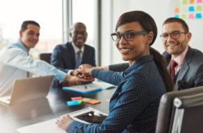 Successful African American team leader turning to smile at the camera as her multiracial team of executives links hands across the table
